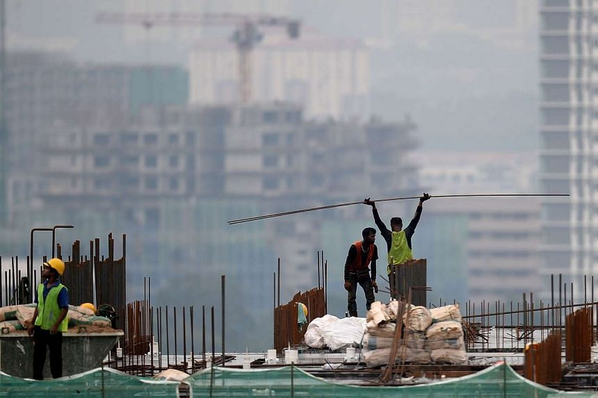 A worker carries building material at a construction site in Kuala Lumpur on May 4, 2016.