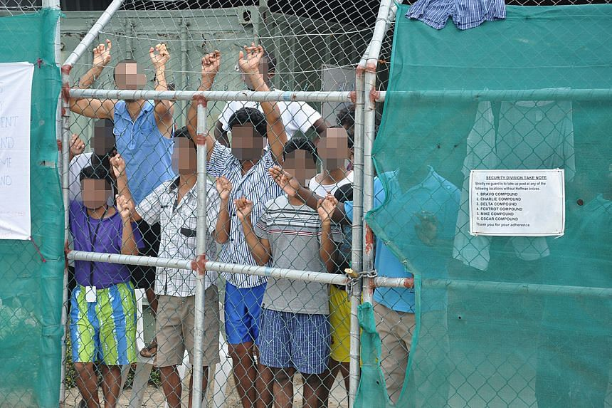 Asylum-seekers look through a fence at the Manus Island detention centre in Papua New Guinea, on March 21, 2014.
