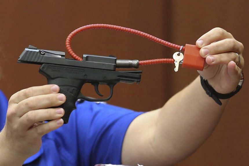 A crime scene technician for the Sanford Police Department showing the jury Mr George Zimmerman's gun, which was used to kill Trayvon Martin, during Mr Zimmerman's trial in Sanford, Florida, on June 25, 2013.
