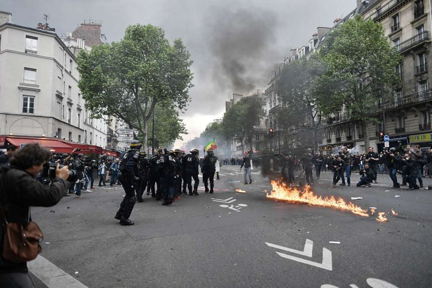 Riot police standing next to a fire during a protest against the French government's labour reform, in Paris on May 12, 2016.