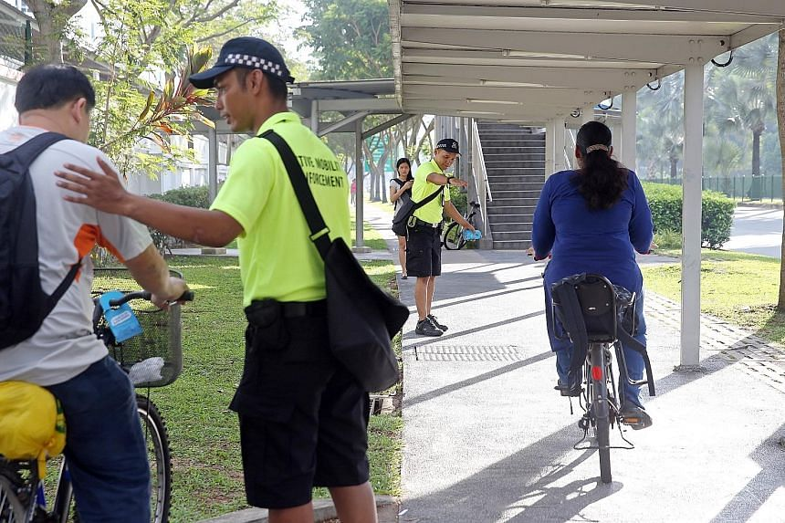 Active Mobility Enforcement Team officers keeping an eye on cyclists and people using personal mobility devices in Woodlands Avenue 7 yesterday morning. They handed out brochures with safety tips for cyclists and also issued advisory notices to those