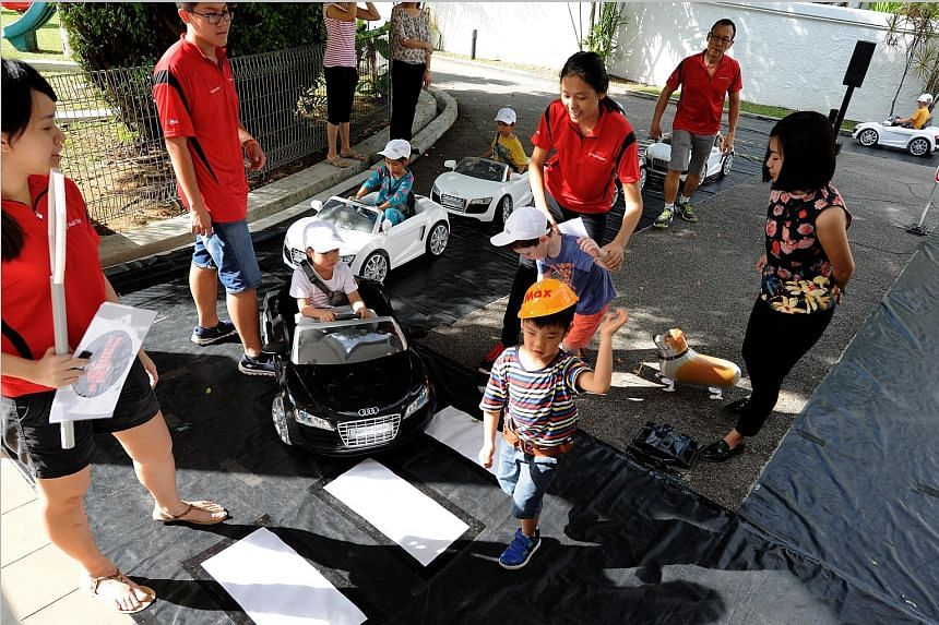 Pre-schoolers from Pat's Schoolhouse getting a feel of the road in Audi R8 mini-electric cars and as pedestrians crossing the street while being supervised by staff from the Singapore Toy Club yesterday. They were in an interactive road safety progra