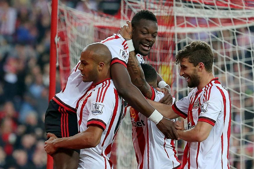 Sunderland's Lamine Kone (top) celebrates after scoring his team's third goal during the English Premier League football match between Sunderland and Everton.