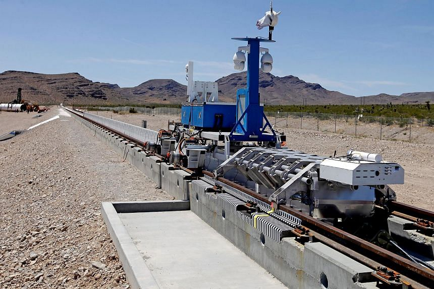 A recovery vehicle and a test sled sit on rails after the first test of the propulsion system at the Hyperloop One Test and Safety site on May 11, 2016 in Las Vegas, Nevada.