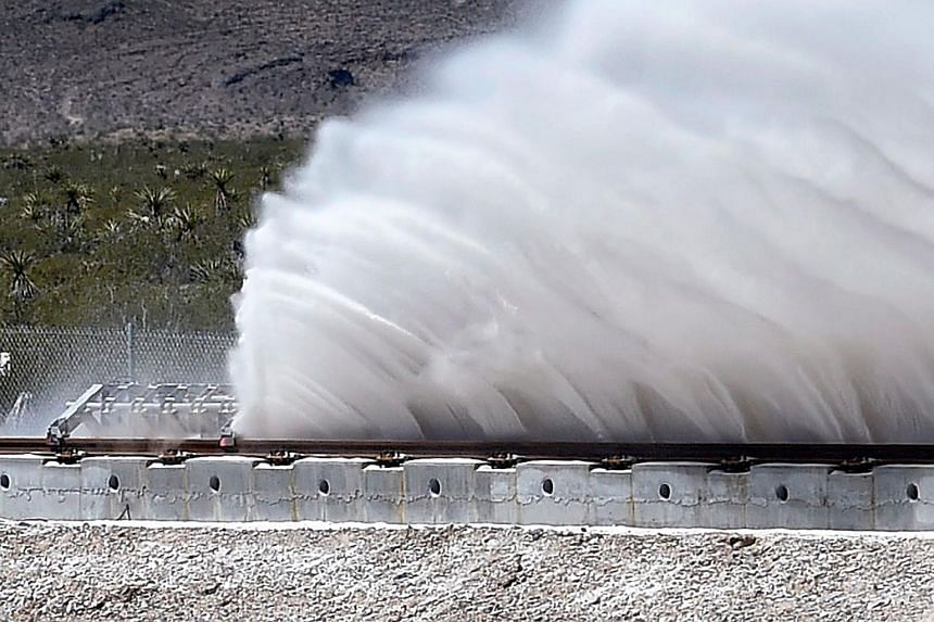 Sand is displaced as a test sled is slowed during the first test of the propulsion system at the Hyperloop One Test and Safety site on May 11, 2016 in North Las Vegas, Nevada.
