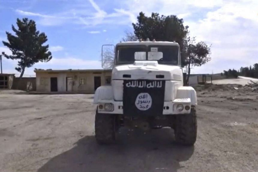 A truck bearing what appears to be an ISIS flag within an oil facility near Al-Shadadi, Syria.