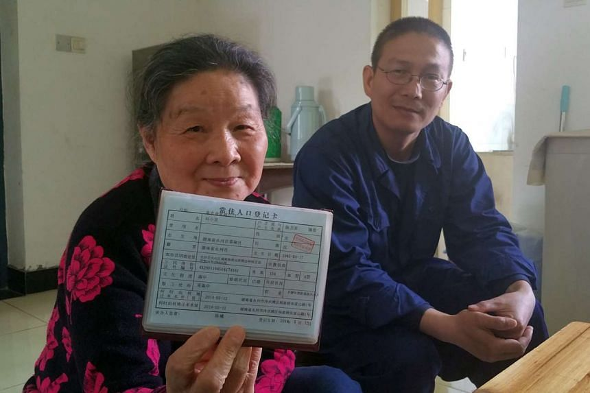 Madam Liu Xiaolong, 71, with her elder son Yu Cong at her younger son Yu Bo's apartment in Changsha city. She is holding up her household registration booklet, which she updated in 2014 as a Changsha resident again, some 50 years after she was sent d