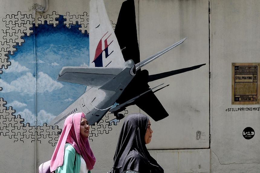 Malaysian women walk in front of a mural of missing Malaysia Airlines MH370 plane in a back-alley in Shah Alam on Mar 8, 2016.