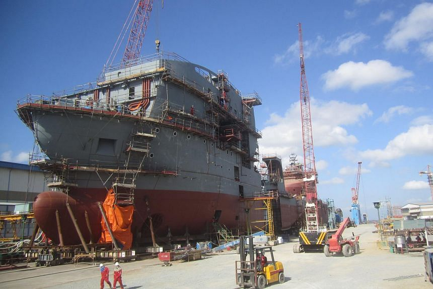 Workers pass a vessel being built at Vard's shipyard in Vung Tau, southern Vietnam.