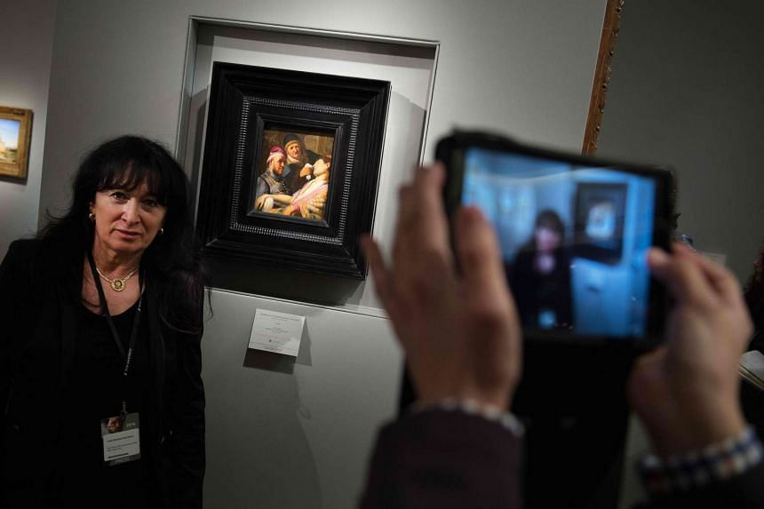 """A woman poses with the painting """"The Unconscious Patient"""" by Rembrandt van Rijn."""