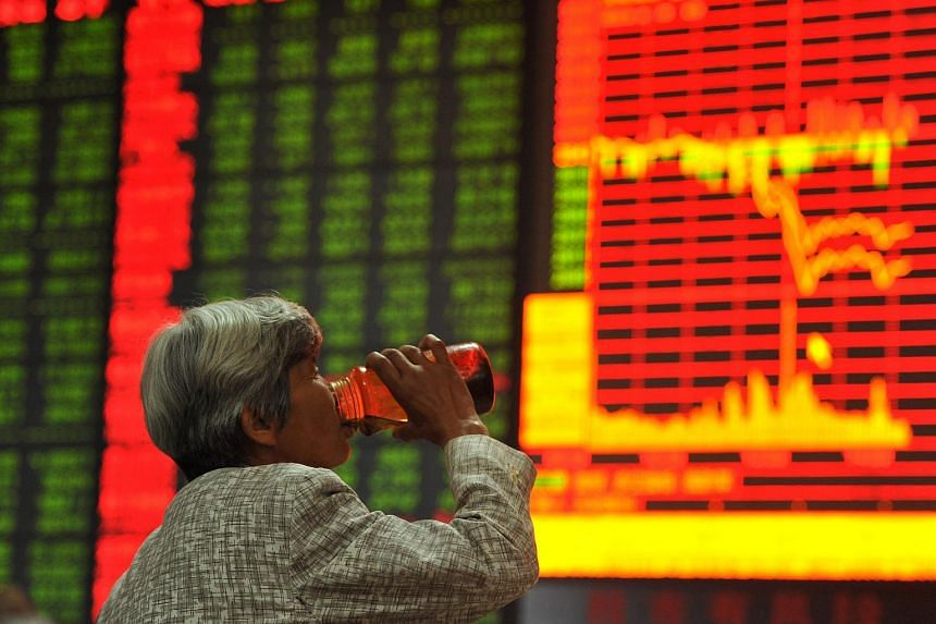 An investor drinks tea in front of a screen showing stock market movements at a securities firm in Fuyang, China.