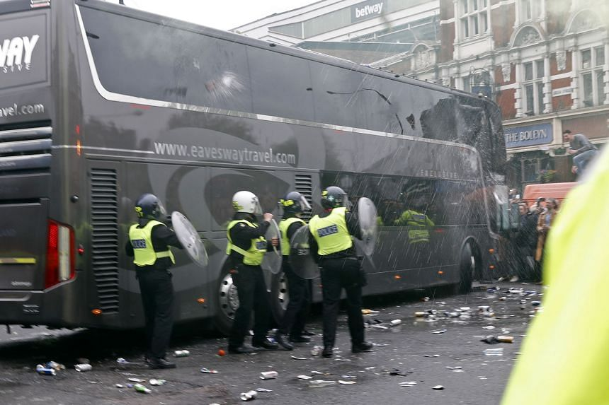 As bottles and other debris litter the street, riot police armed with shields take up their positions beside the Manchester United team bus, which was damaged in the pre-game attack on Tuesday.