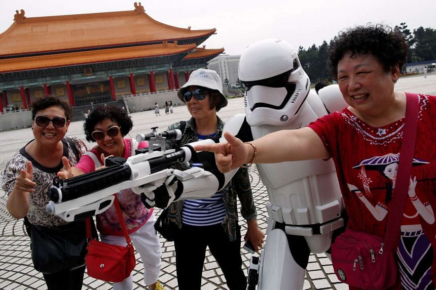 """Tourists from China pose with a man dressed as a Storm Trooper from """"Star Wars"""" during Star Wars Day in Taipei, Taiwan on May 4, 2016."""