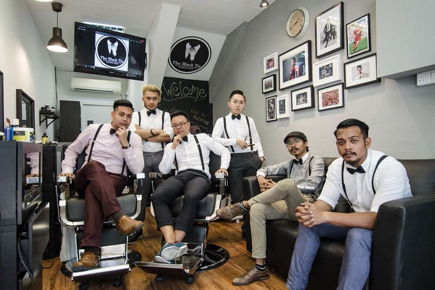 Mr Muhammad Tirmidzi Saad (leftmost) and Mr Melvin Koh (third from left), both 31, opened gentleman's barber shop The Black Tie in at the bottom of a Jurong West block last month. With them are their store manager and barbers, who are all aged betwee