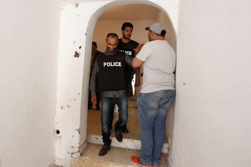Tunisian police officers pass near a bullet-riddled house damaged during the operation.