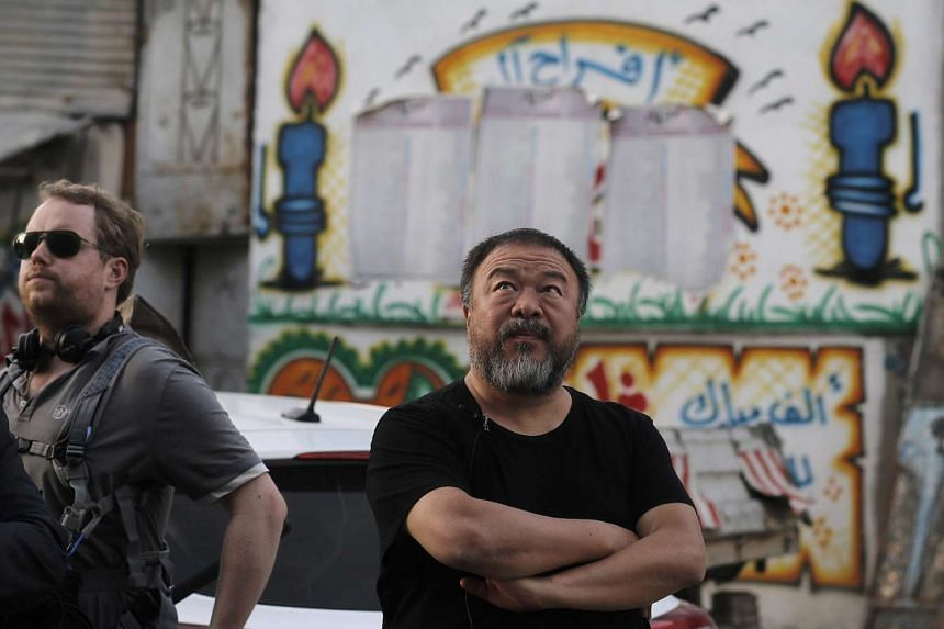 Ai Weiwei (right) looks on while filming a documentary about Palestinian refugees in the streets of Jabaliya refugee camp.