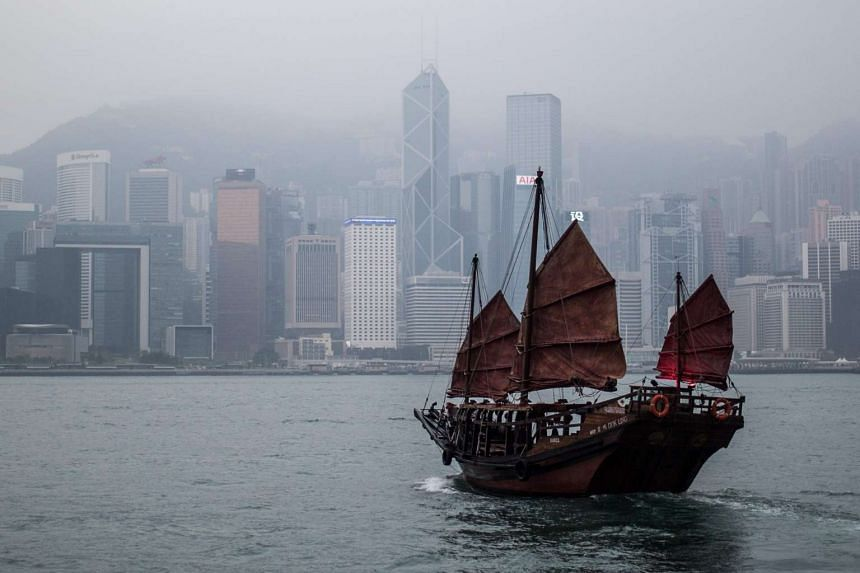 A traditional junk sails in Victoria Harbour against the skyline in Hong Kong, on March 30, 2016.