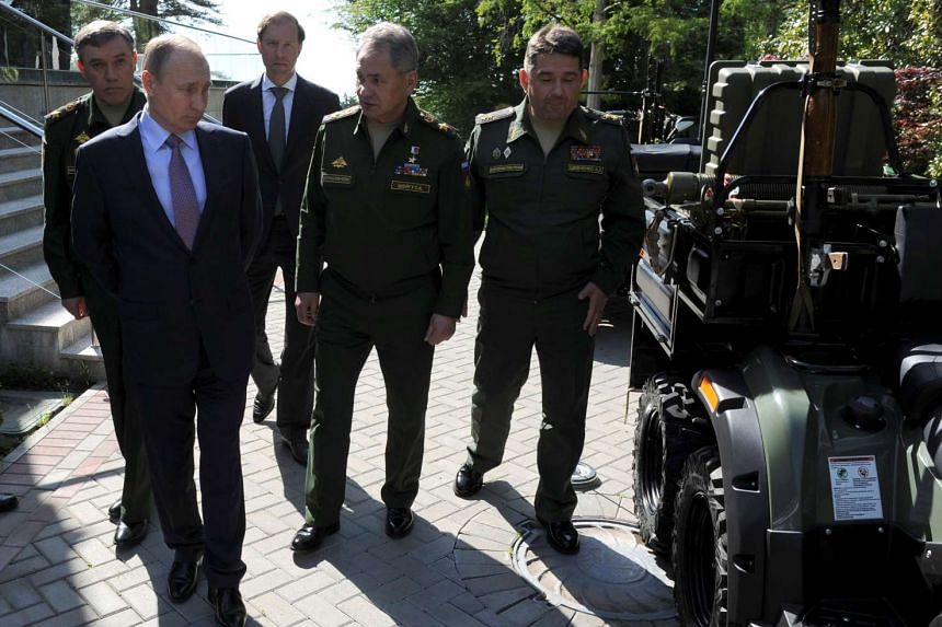 Russian President Vladimir Putin (second from left) inspects military vehicles after a meeting with military and defence industries' officials in Sochi, Russia, on May 12, 2016.