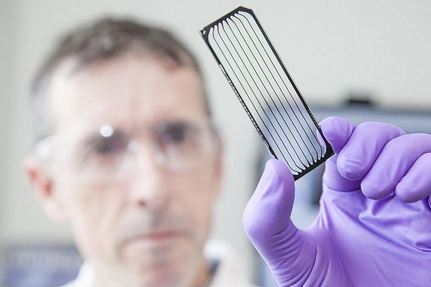 A scientist looking at a flow cell as part of cancer research. Among the game changers identified by cancer experts are cellular immunotherapy and nanotechnology.