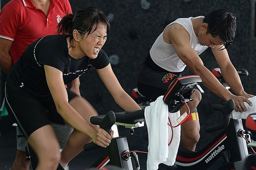 Triathlete Winona Howe (in black) and former S-League player Hilmi Azman were put through their paces on a stationary watt bike yesterday. The two are among 145 cyclists hoping to get a place in the national training squad.