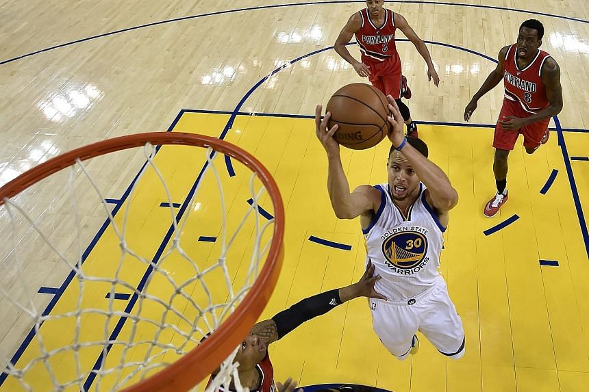 Golden State Warriors star Stephen Curry, the newly- crowned league Most Valuable Player, powering ahead of Portland Trail Blazers players to score two of his 29 points in Game 5 of the NBA Western Conference semi-finals. The Warriors won the series