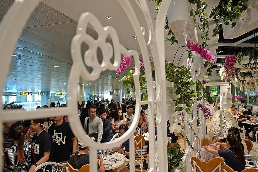 Many people queued for hours at Terminal 3 yesterday to be among the first to dine in the Hello Kitty-themed cafe (above), which is the world's first to be open round the clock. The cafe's menu (left) is Singapore-inspired, with dishes such as wagyu