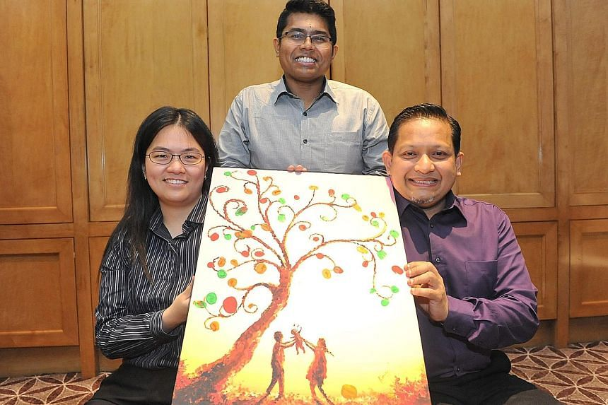 Mr Mohamed Fazly (centre), assistant director, community policy, at Singapore Prison Service, with Ms Edlyn Tan and Mr Mohamed Fawzi Ali, both volunteers with the Yellow Ribbon Community Project. The painting they are holding is the work of former of