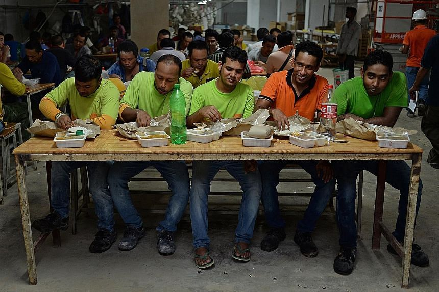 Workers from Unison Construction having their lunch at their worksite on Wednesday. Unison is one of three firms participating in a pilot programme run by social enterprise 45Rice that ensures hot meals are delivered to foreign workers thrice a day.