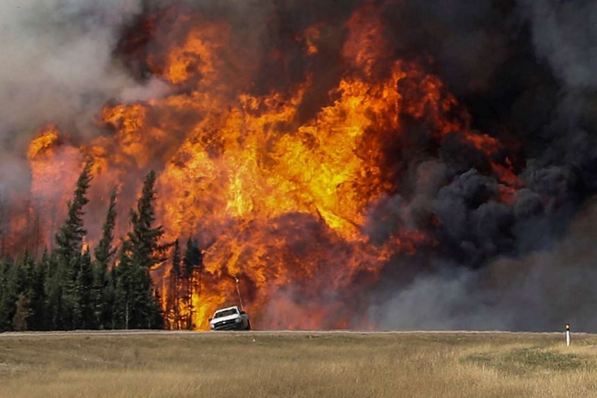 Smoke and flames from the wildfires erupt behind a car on the highway near Fort McMurray, Alberta, Canada, on May 7, 2016.