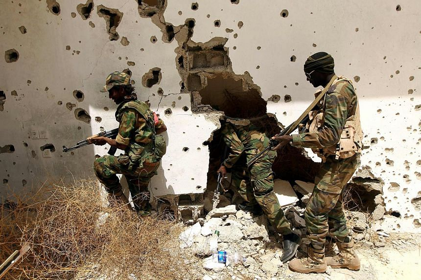Libyan pro-government forces patrolling an area on the outskirts of Benghazi on April 19.