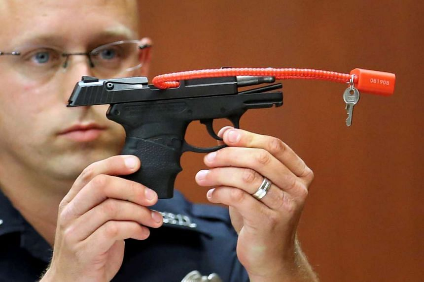 A police officer holds up the gun in court in 2013.