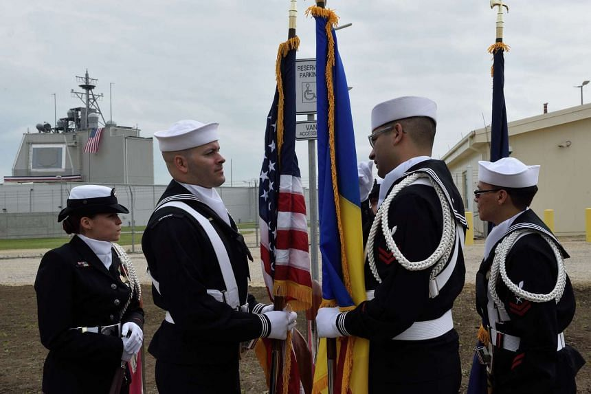US Army personnel stand with the Romanian and US flags during an inauguration ceremony of the US anti-missile station Aegis Ashore.