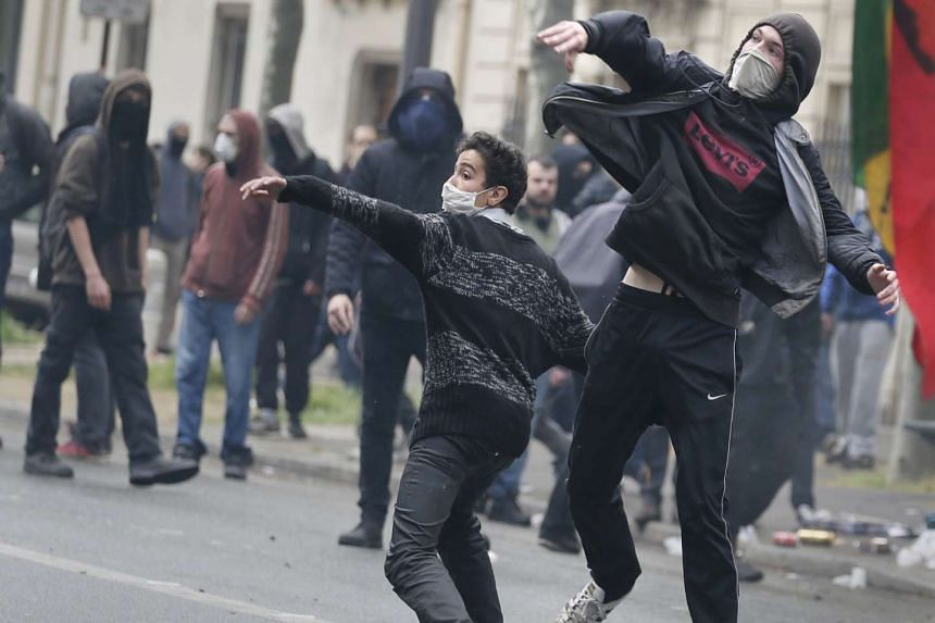 Protesters throw projectiles during a demonstration against French labour law reform in Paris on May 12, 2016.