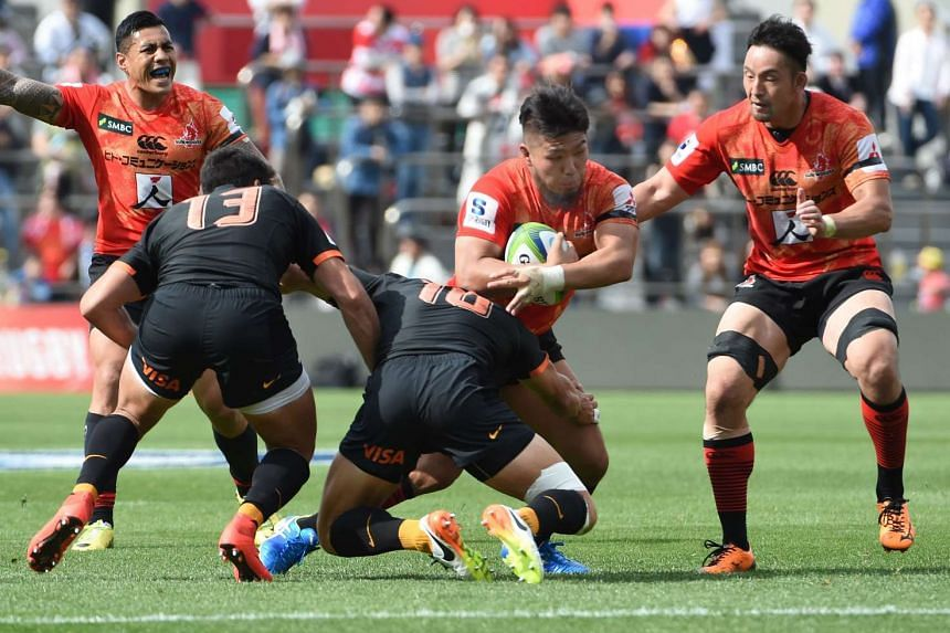 Shota Horie (centre) of the Sunwolves is tackled by Juan Martin Hernandez of the Jaguares during the Super Rugby match between Japan's Sunwolves and Argentina's Jaguares in Tokyo on April 23, 2016.