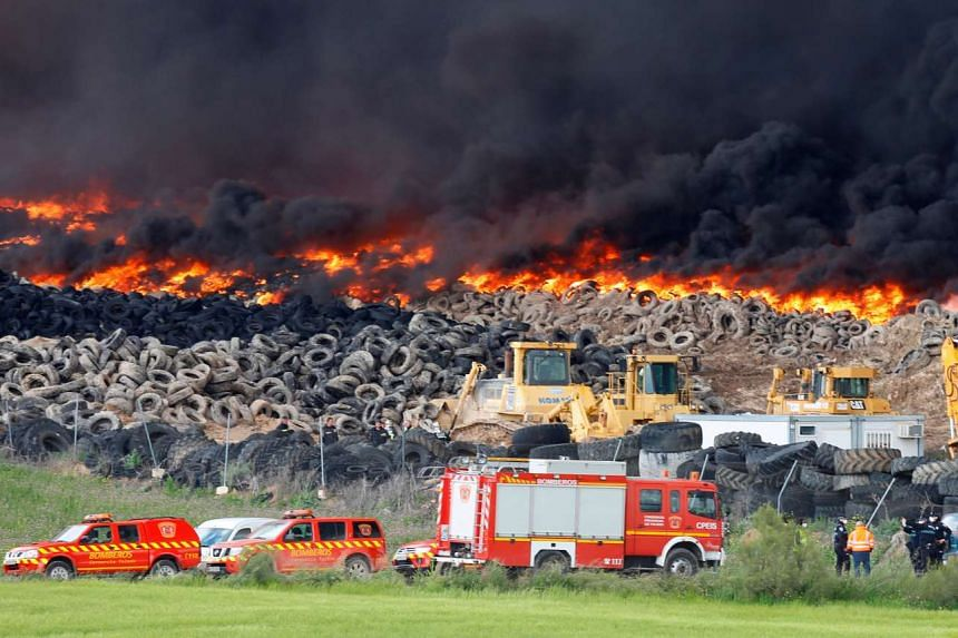 Emergency workers stand next to the huge blaze on May 13, 2016.