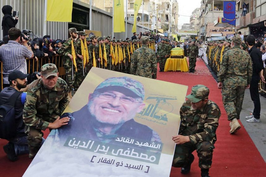 Hezbollah members hold a picture of Mustafa Badreddine in front of his coffin during his funeral in Lebanon, on May 13, 2016.