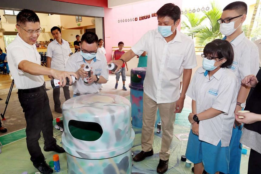 (From left to right) Artist Cheng Ya Jie, Bryan Ng Jin Ming, and Acting Minister for Education Ng Chee Meng spray painting a dustbin.