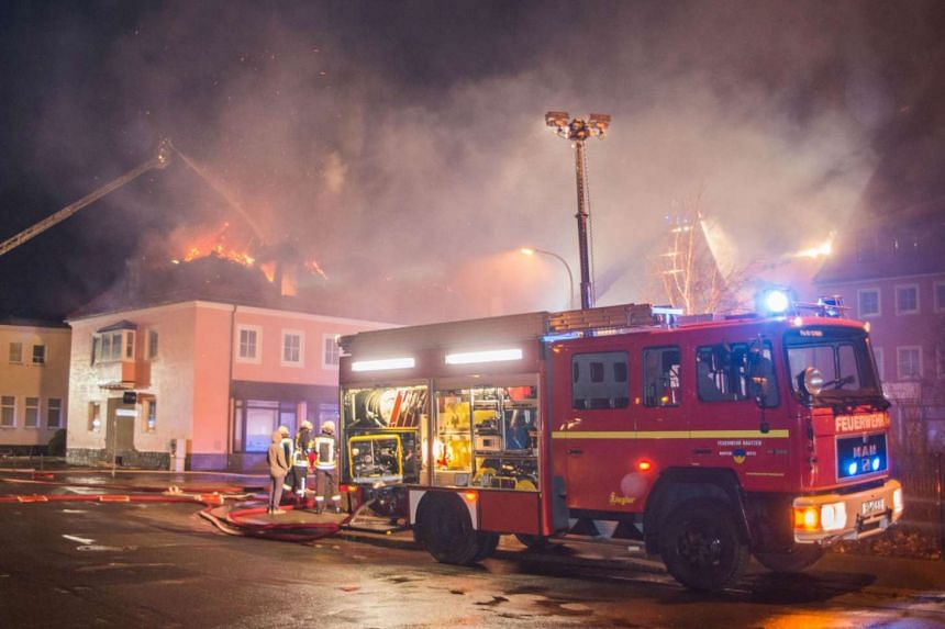 Firemen extinguishing a fire at a former hotel under reconstruction to become a home for asylum seekers on Feb 21, 2016, in Bautzen, Eastern Germany.