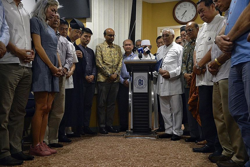 Deputy Prime Minister Tharman Shanmugaratnam, Parliamentary Secretary Baey Yam Keng, religious leaders from the Inter-Religious Organisation (IRO) and guests observing a minute of prayer for Mr Heng at the IRO office yesterday.