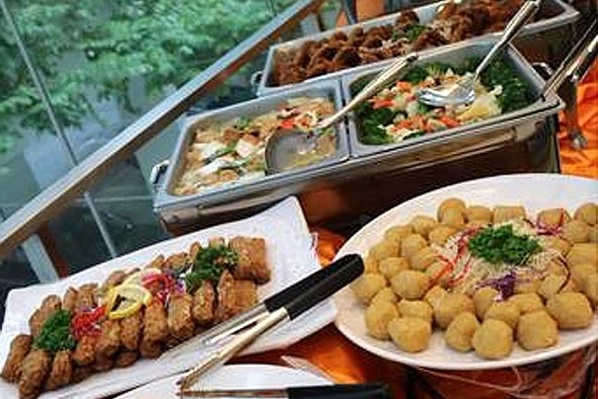 A birthday-party buffet spread in Pasir Ris provided by Kuisine Catering on Feb 13 (top). The Kuisine Catering premises were shuttered and delivery vans were seen nearby when ST visited on Feb 19.