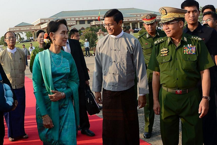Ms Suu Kyi at the Naypyitaw city airport last Friday with military chief Senior General Min Aung Hlaing (right). He said the army reported important matters, when necessary, to Ms Suu Kyi.