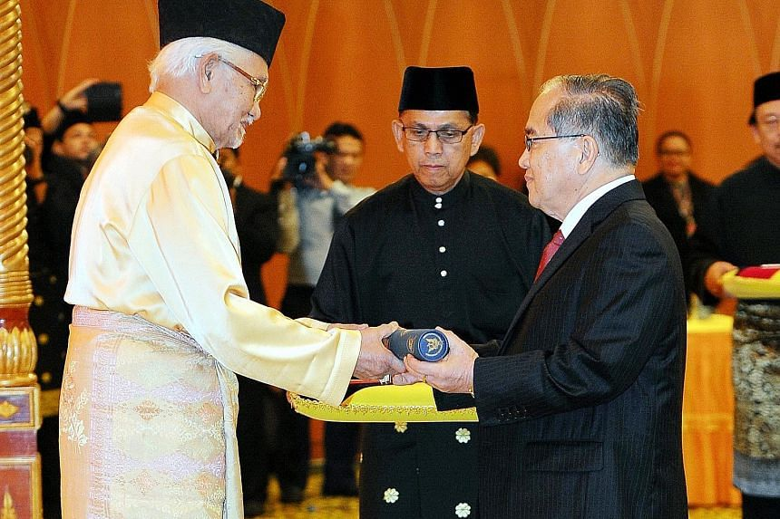 Sarawak Governor Tun Abdul Taib Mahmud (left) presenting the letter of appointment as a member of the Sarawak Cabinet to Datuk Amar Douglas Uggah Embas during the swearing-in ceremony at the Sarawak State Legislative Building yesterday.