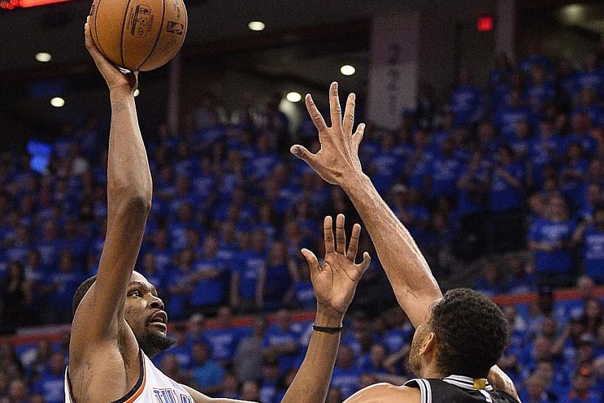 Oklahoma City forward Kevin Durant shoots over San Antonio forward Tim Duncan as Spurs guard Manu Ginobili looks on. The Thunder overcame the Spurs 113-99 and will next face Golden State.