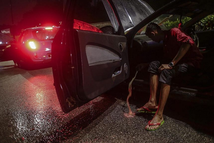 A man scoops water from his car after flash floods hit Kuala Lumpur, causing severe traffic jams and even trapping some people in their vehicles. Officials say they are looking into ways to mitigate the flooding.