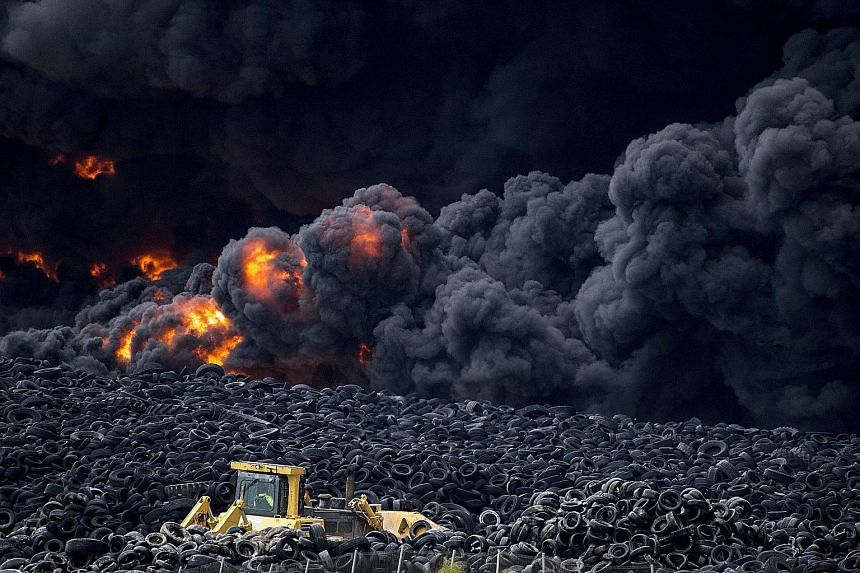 Flames raging through a pile of tyres at a massive waste ground south of the Spanish capital of Madrid yesterday. The 10ha dump, which contains millions of tyres, caught fire early yesterday morning, releasing a thick black cloud of toxic fumes. Offi
