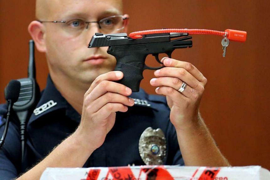 A police officer displays the gun in court in 2013.
