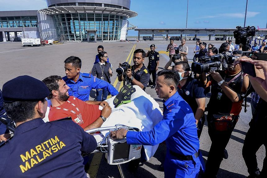 David Hernandez Gasulla of Spain (second from left) is transported away on a stretcher after arriving on a Maritime Malaysia Bombardier 415 aircraft at Kota Kinabalu International Airport on May 13, 2016.
