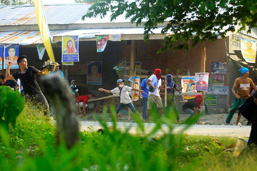 Supporters of a local candidate throwing stones at supporters of a rival candidate during a clash in Maguindanao, on May 8, 2016.