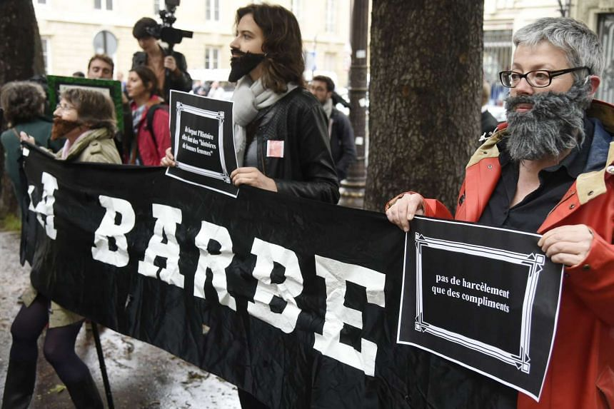 """A group of women with beard hold a banner reading """"the beard"""" (French expression """"la barbe"""" meaning """"enough"""") and """"No harassment, only compliments"""" during a rally against the sexual harassment of women in front of the National Assembly in Paris, on M"""