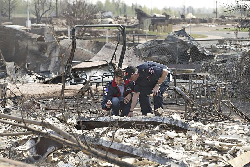 "Canadian Prime Minister Justin Trudeau (left) and Fort McMurray fire chief Darby Allen visiting a neighbourhood that was devastated by a wildfire that forced the evacuation of the city of Fort McMurray, in Alberta, Canada, on Friday. Known as ""the be"